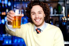 Happy man offering glass of beer, let's celebrate Stock Image