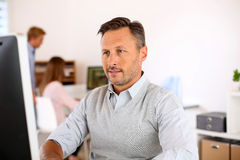Happy man in office sitting in front of computer Royalty Free Stock Photo