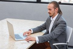 Happy man in the office sitting and working with lap top . Business concept. royalty free stock photos