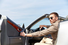 Happy man opening door of cabriolet car outdoors Royalty Free Stock Photo