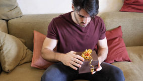 Happy man opening gift or present. Smiling handsome surprised young man opening small gift stock image