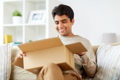 Happy man opening parcel box at home royalty free stock photography
