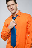 Happy man in orange shirt and blue tie. Stock Photography