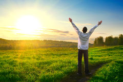 Happy man outdoor. Happy man with hands up on sunset background stock photography