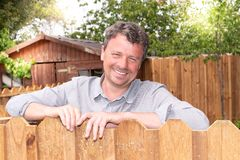 Happy man outdoor handsome smiling middle aged guy in home garden with wood hut. A Happy man outdoor handsome smiling middle aged guy in home garden with wood royalty free stock photography