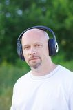 Happy man outdoors in wireless headset Royalty Free Stock Images