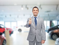 Happy man over auto show or car salon background stock photography