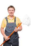 Happy man in overalls holding a mop. On a white background isolated Stock Images