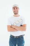 Happy man with paint roller standing arms crossed Stock Photos