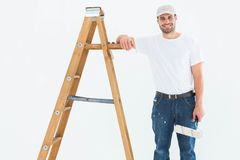 Happy man with paint roller standing by ladder Royalty Free Stock Image