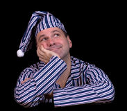 Happy man in pajamas. Dreaming on a black background Royalty Free Stock Photo