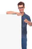 Happy man with panel, pointing. Casual young man holds a blank panel and points at you while smiling. isolated on a white background Stock Images