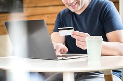 Happy man paying with credit card or using online bank. stock photo