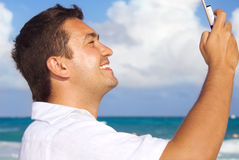 Happy man with phone on the beach Stock Image