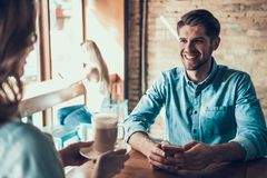 Happy man with phone sits in coffee shop with girl. Happy men with phone sits in coffee shop with girl. Date in cafeteria Royalty Free Stock Photos