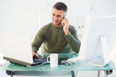 Happy man phoning and using laptop Stock Image
