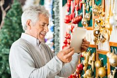 Happy Man Photographing Christmas Ornaments At Royalty Free Stock Photos