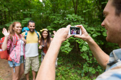 Happy man photographing friends by smartphone Royalty Free Stock Photography