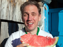 The happy man with a piece of a water-melon Stock Photos