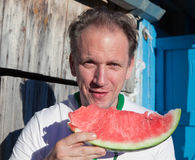 Happy man with a piece of a water-melon Stock Image