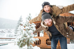Happy man piggibacking his girlfriend and laughing in winter. Happy handsome bearded men piggibacking his girlfriend and laughing in winter Royalty Free Stock Image