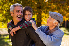Happy man piggybacking son while with father at park Stock Photo
