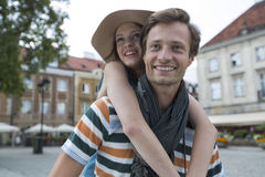 Happy man piggybacking woman on street during vacation Stock Photos