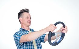 Happy man in a plaid shirt is driving a car holding the steering wheel. Driver concept royalty free stock image