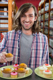 Happy man with a plate of cupcakes Royalty Free Stock Photos