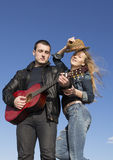 Happy man playing acoustic guitar with woman who taking off her hat. Stock Images