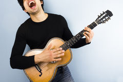 Happy man playing acoustic guitar. Young multiracial man passionately playing guitar and singing Stock Images