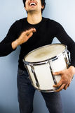 Happy man playing drum. Happy young multiracial man playing a drum Royalty Free Stock Photos