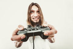 Happy man playing games. Playing games. Young smiling cheerful man play on console xbox playstation. Guy with pad joystick Stock Photos