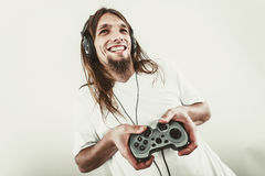 Happy man playing games. Playing games. Young smiling cheerful man play on console xbox playstation. Guy with pad joystick Stock Image