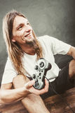 Happy man playing games. Playing games. Young smiling cheerful man play on console xbox playstation. Guy with pad joystick Stock Photography