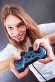 Happy man playing games. Playing games. Young smiling cheerful man play on console xbox playstation. Guy with pad joystick Stock Images