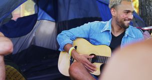 Man playing guitar for his friends at a music festival 4k. Happy man playing guitar for his friends at a music festival 4k stock video