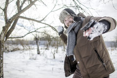 Happy man playing with snowballs Stock Photography