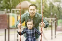 Happy man playing on a swing with his daughter stock photo
