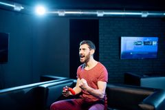 Happy man playing video games with gaming console in the club stock photography