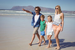 Happy man pointing away with family walking at beach Royalty Free Stock Photography