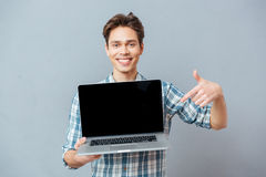 Happy man pointing finger on blank laptop screen Royalty Free Stock Photos