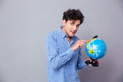 Happy man pointing finger on globe Royalty Free Stock Photo
