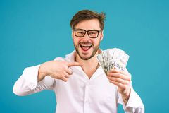 Happy man pointing at pile of dollars royalty free stock photography