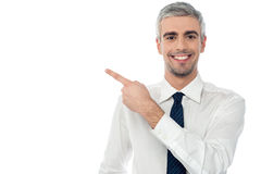 Happy man pointing at something. Smiling man pointing his finger on the copyspace Royalty Free Stock Photos