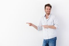 Happy man pointing to right. Happy young man standing over white background, pointing to right, smiling at camera Stock Photography
