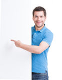 Happy man points finger on a blank banner. Stock Photos