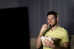 Happy man with popcorn watching tv at night Royalty Free Stock Photography