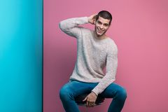 Happy man portrait. Young handsome man. Studio fashion portrait. Close-up portrait of sensual young model staying  on chair in studio on mixed blue pink Royalty Free Stock Photos