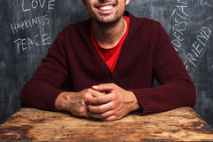 Happy man with positive thoughts. Happy man is sitting at a school desk. Blackboard in background has positive words written on it Stock Photo